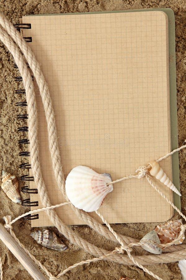 Libro de ejercicio y seashell imagen de archivo