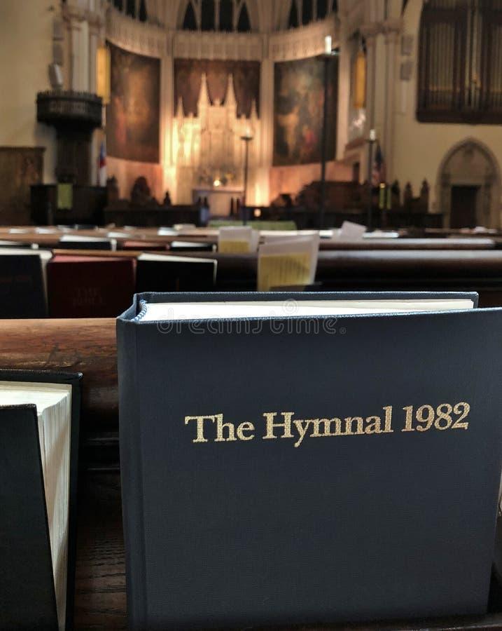 Libro de la biblia dentro del banco de la iglesia y de las filas del banco que asientan el lugar de culto religioso y que ruegan foto de archivo libre de regalías