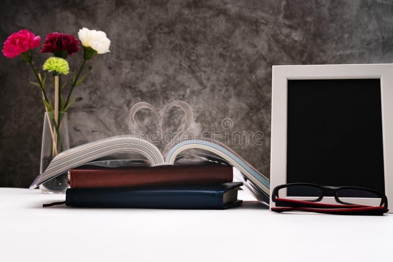 Libro de la historia de amor con la página abierta de la literatura en forma del corazón y del bastidor de la foto para escribir  fotos de archivo libres de regalías