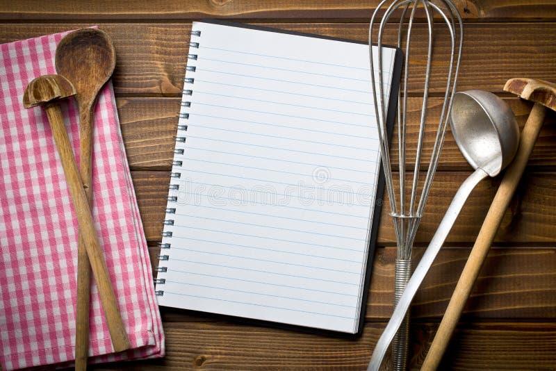 Libro de la receta con artículos de cocina fotografía de archivo