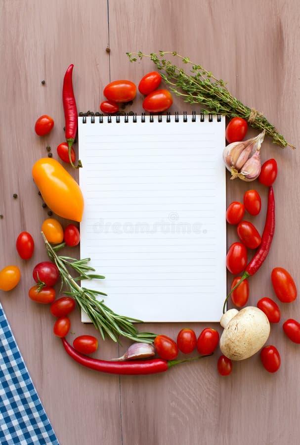 Libro de la receta con las verduras frescas y las hierbas en de madera imagen de archivo