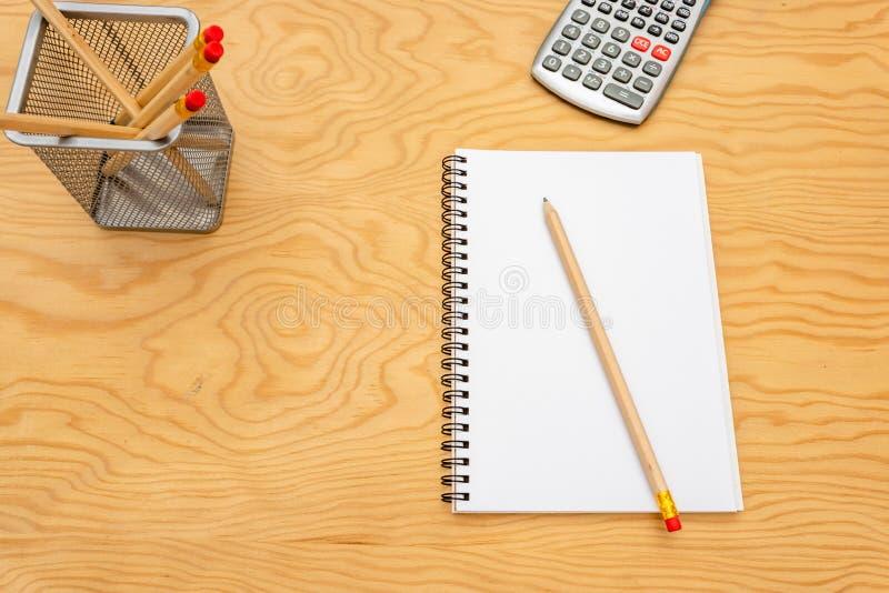 Libro de la visi?n superior, calculadora, vidrios en la tabla de madera fotografía de archivo