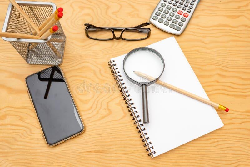 Libro de la visi?n superior, calculadora, vidrios en la tabla de madera fotografía de archivo libre de regalías