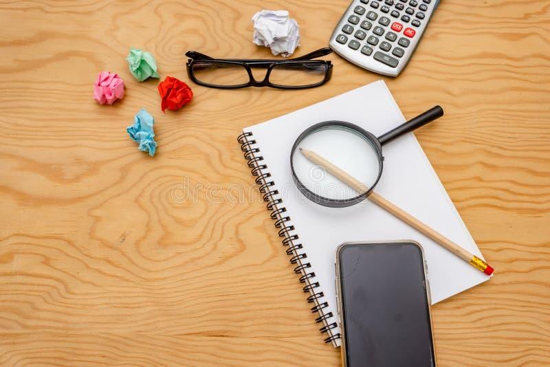 Libro de la visi?n superior, calculadora, vidrios en la tabla de madera foto de archivo