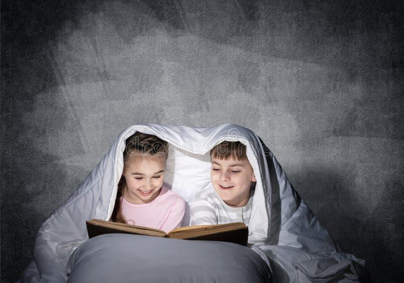 Libro de lectura absorbido de la ni?a y del muchacho imágenes de archivo libres de regalías