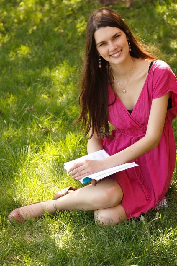 Libro de lectura adolescente de la muchacha del estudiante atractivo alegre al aire libre imagenes de archivo