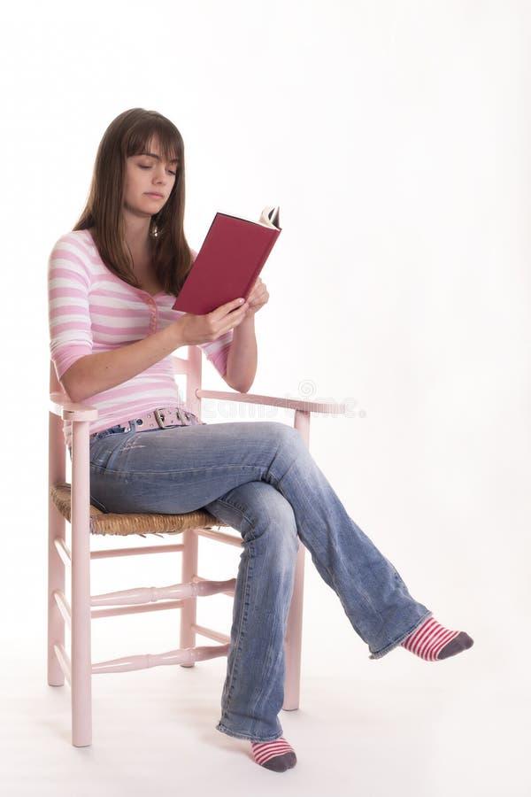 Libro de lectura adolescente de la muchacha en silla fotos de archivo libres de regalías