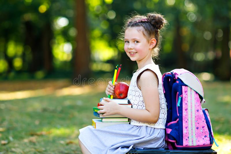 Libro de lectura adorable feliz de la muchacha del niño y libros de la tenencia diversos, manzanas y lápices coloridos en el prim foto de archivo