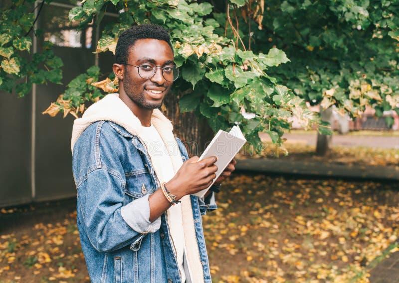 Libro de lectura africano sonriente creativo del hombre del retrato en otoño imagen de archivo libre de regalías