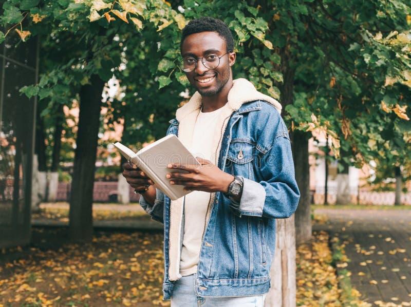 Libro de lectura africano sonriente feliz del hombre del retrato en otoño foto de archivo libre de regalías