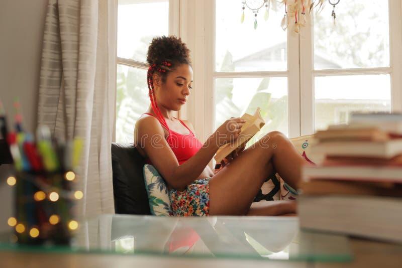 Libro de lectura afroamericano de la mujer en casa cerca de la ventana imagen de archivo libre de regalías
