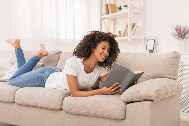 Libro de lectura afroamericano hermoso de la muchacha en casa foto de archivo libre de regalías