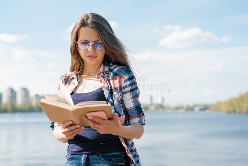 Libro de lectura al aire libre de la mujer adulta del retrato Calle del fondo, ciudad, río foto de archivo libre de regalías