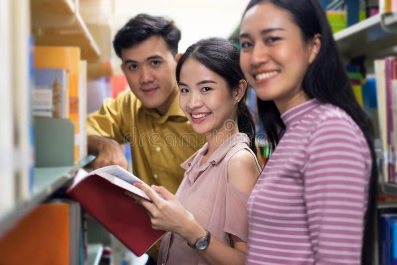 Libro de lectura asiático del grupo de estudiantes en concepto de la biblioteca, del aprendizaje y de la educación fotos de archivo