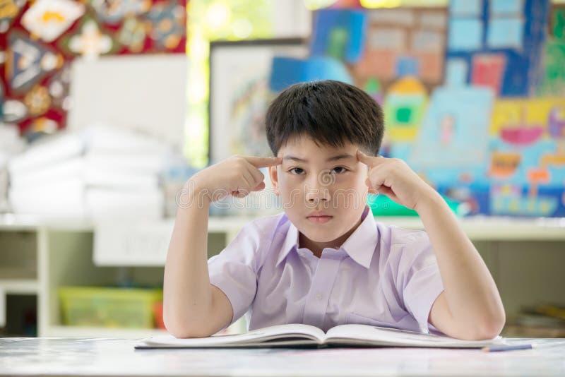 Libro de lectura asiático feliz del niño y pensamiento en eso fotos de archivo libres de regalías