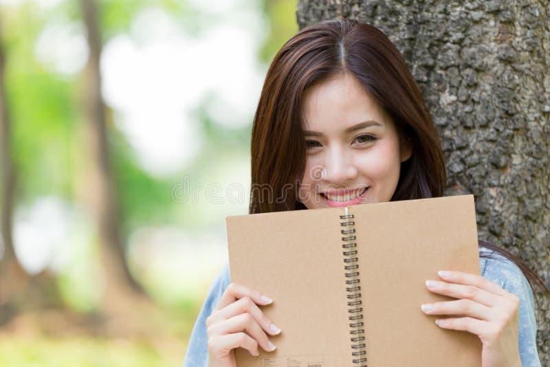 Libro de lectura asiático hermoso de la mujer en el parque imágenes de archivo libres de regalías