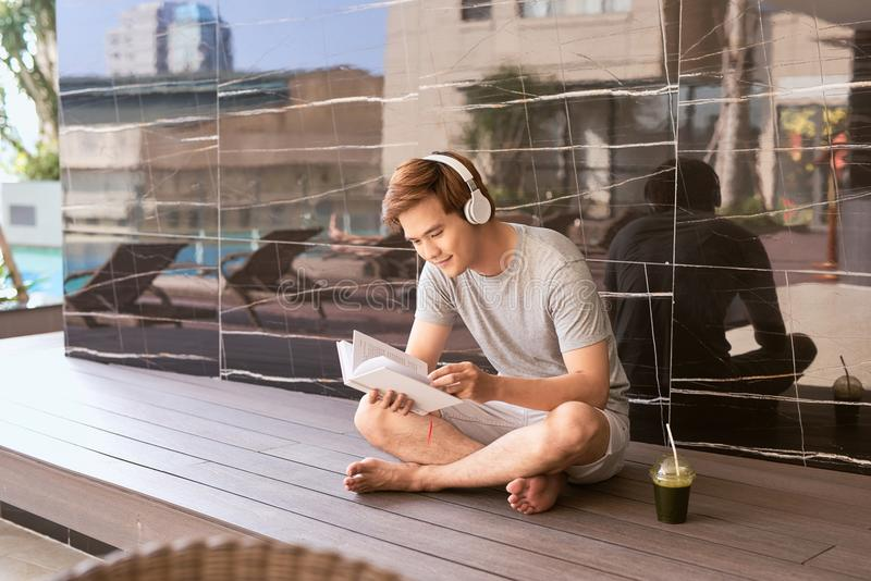 Libro de lectura asiático joven del hombre y el escuchar la música por la piscina imagen de archivo