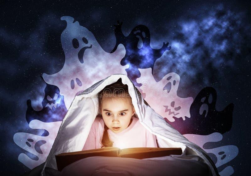 Libro de lectura asustado de la ni?a en cama imagenes de archivo