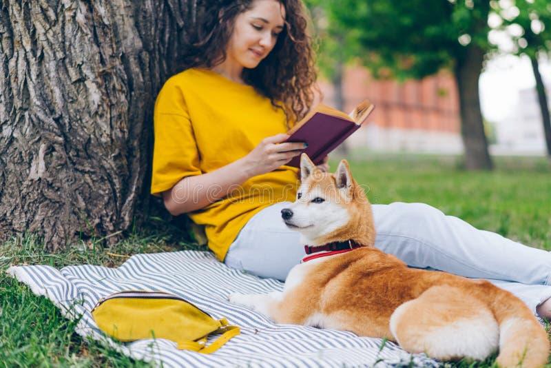 Libro de lectura atractivo del estudiante en el parque que se sienta en césped con el perro del inu del shiba fotografía de archivo