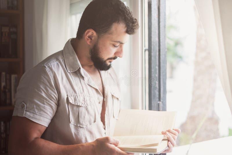 Libro de lectura barbudo del hombre cerca a la ventana imagen de archivo