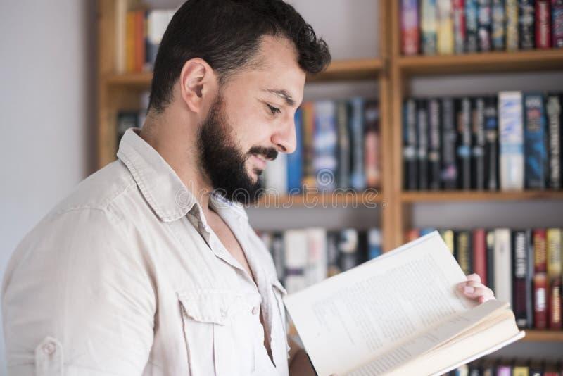 Libro de lectura barbudo del hombre en casa imagen de archivo
