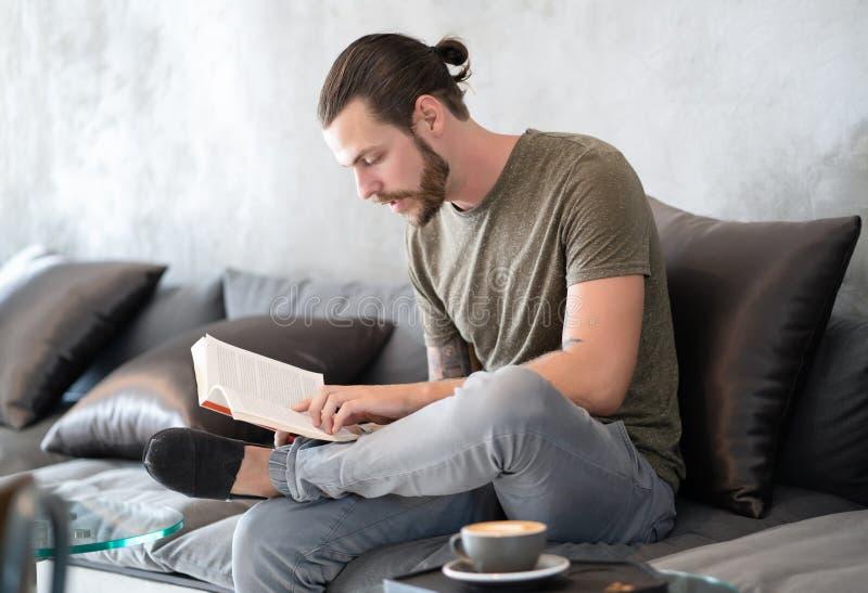Libro de lectura barbudo joven del individuo del inconformista en el café Concepto de la forma de vida imagen de archivo libre de regalías
