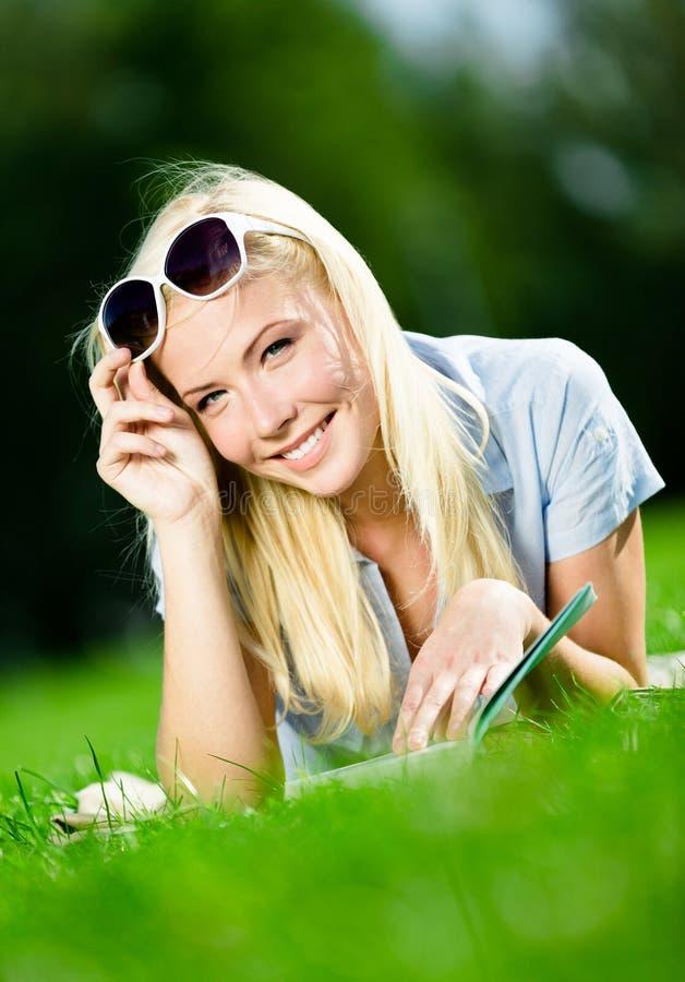 Libro de lectura bonito de la muchacha del estudiante en la hierba fotografía de archivo