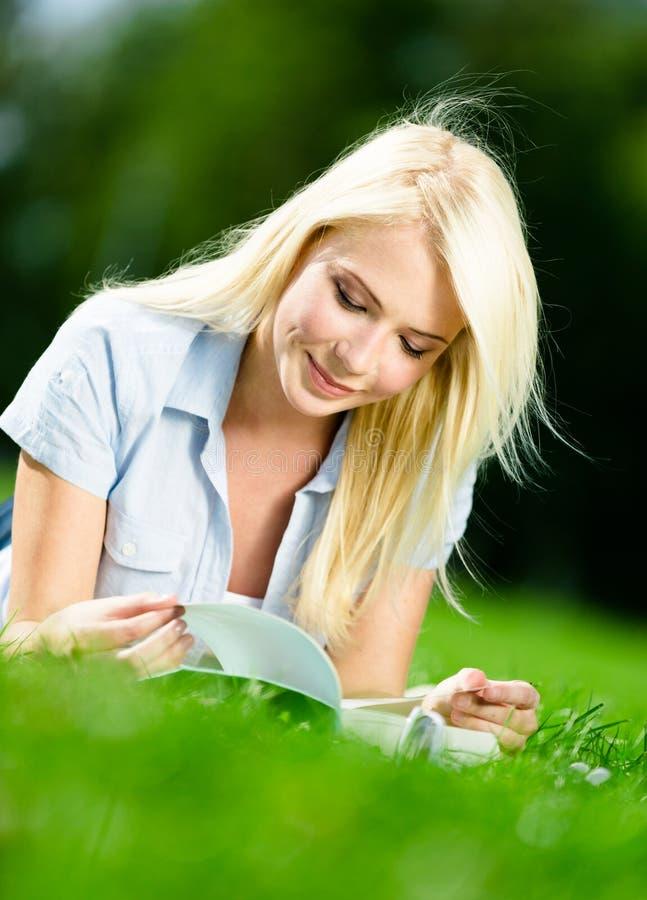 Libro de lectura bonito de la muchacha en la hierba verde imagen de archivo libre de regalías