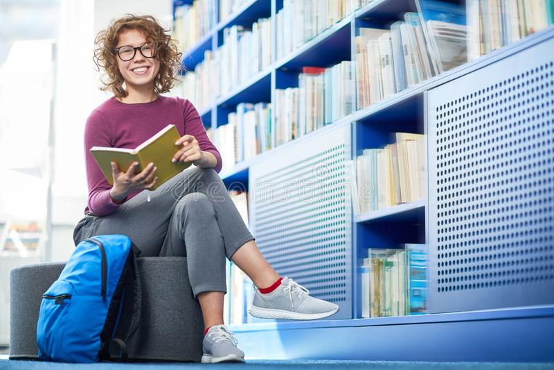 Libro de lectura bonito de la muchacha en biblioteca fotografía de archivo libre de regalías