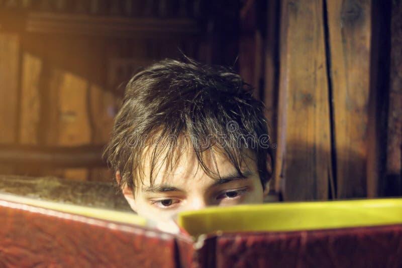 Libro de lectura cabelludo oscuro del hombre que es enfocado fotografía de archivo