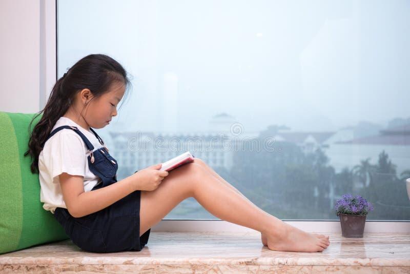 Libro de lectura chino asiático de la niña en el alféizar fotos de archivo