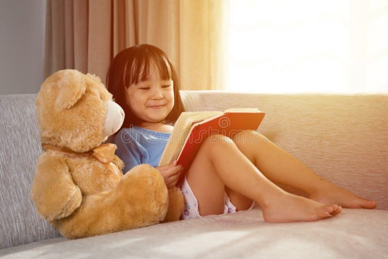 Libro de lectura chino asiático sonriente de la niña con el oso de peluche foto de archivo