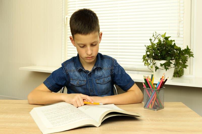 Libro de lectura concentrado del niño pequeño mientras que hace la preparación imagenes de archivo