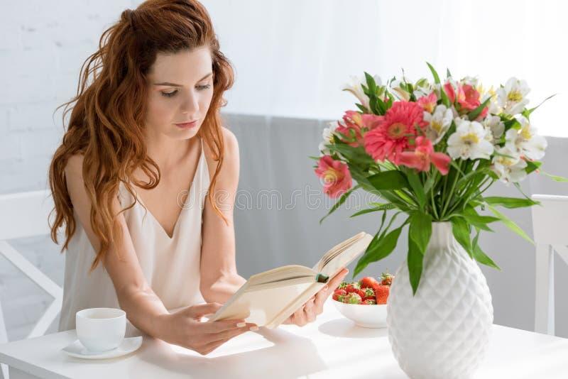 libro de lectura concentrado de la mujer joven mientras que se sienta en la tabla con la taza y las flores de café fotografía de archivo libre de regalías