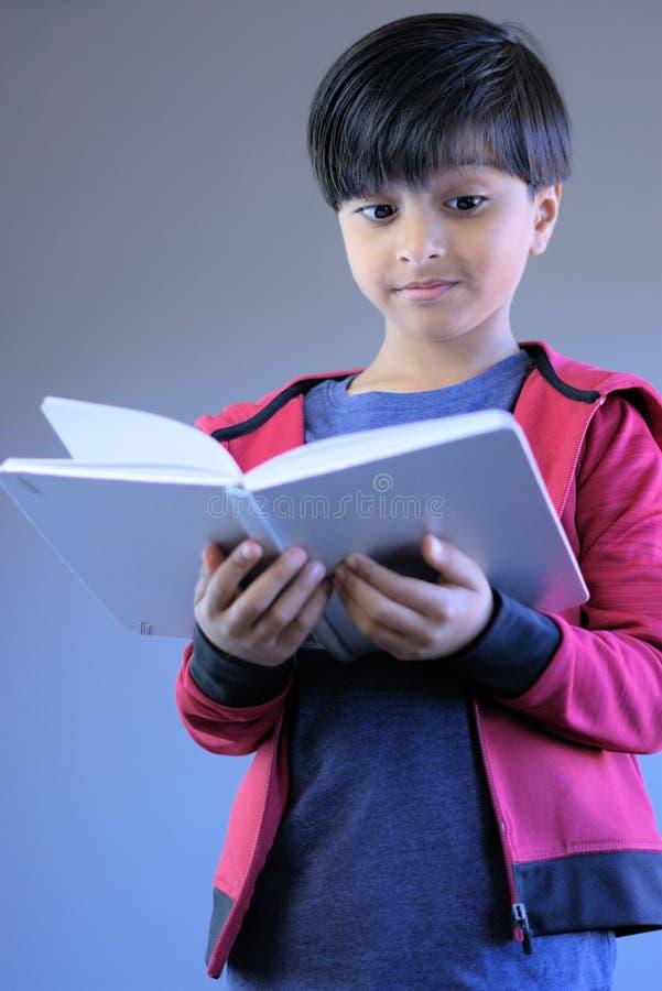 Libro de lectura curioso del niño que mira con la expresión sorprendida fotos de archivo libres de regalías