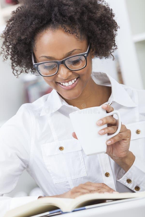 Libro de lectura de consumición del café de la mujer afroamericana fotos de archivo