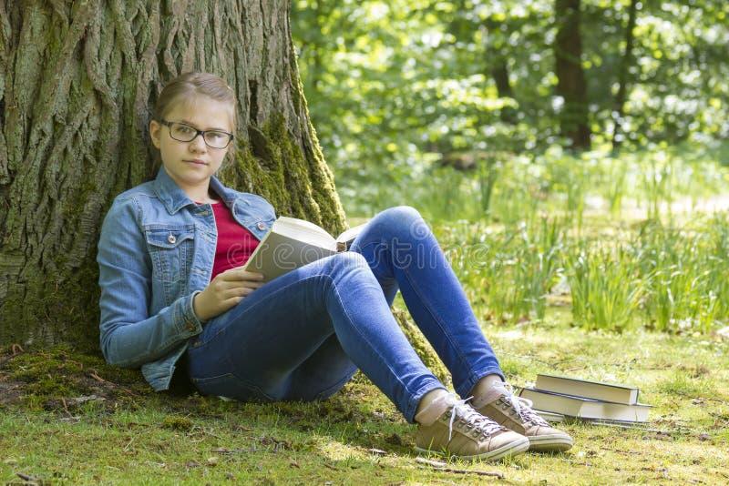 Libro de lectura de la chica joven en parque imagenes de archivo
