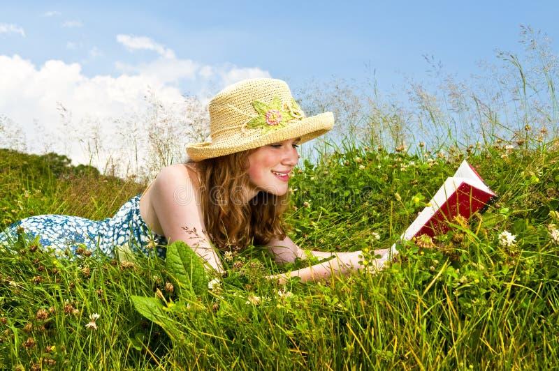 Libro de lectura de la chica joven en prado fotos de archivo libres de regalías