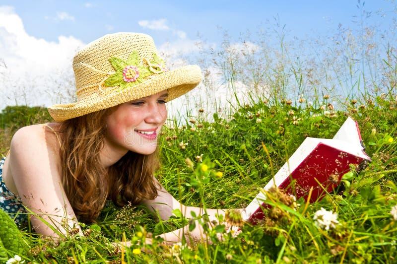 Libro de lectura de la chica joven en prado fotografía de archivo