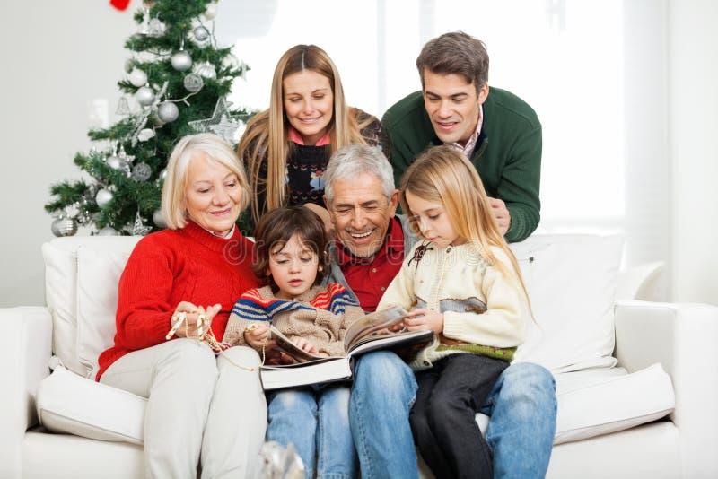 Libro de lectura de la familia junto en casa foto de archivo