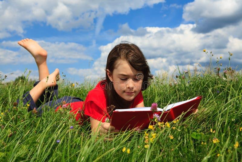 Libro de lectura de la muchacha al aire libre imagen de archivo libre de regalías
