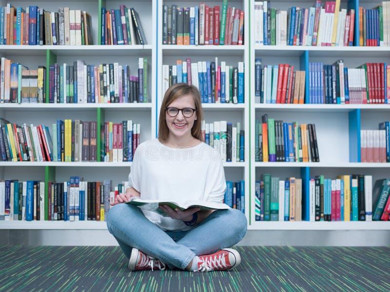 Libro de lectura de la muchacha del estudiante en biblioteca foto de archivo