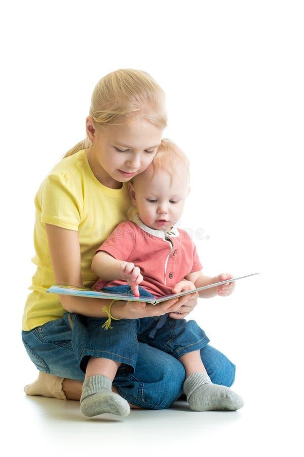 Libro de lectura de la muchacha del niño a su hermano fotografía de archivo libre de regalías