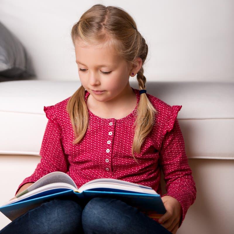 Libro de lectura de la muchacha en casa fotos de archivo libres de regalías