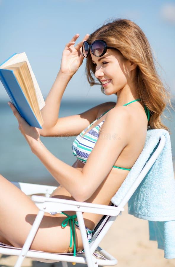 Libro De Lectura De La Muchacha En La Silla De Playa Imágenes de archivo libres de regalías