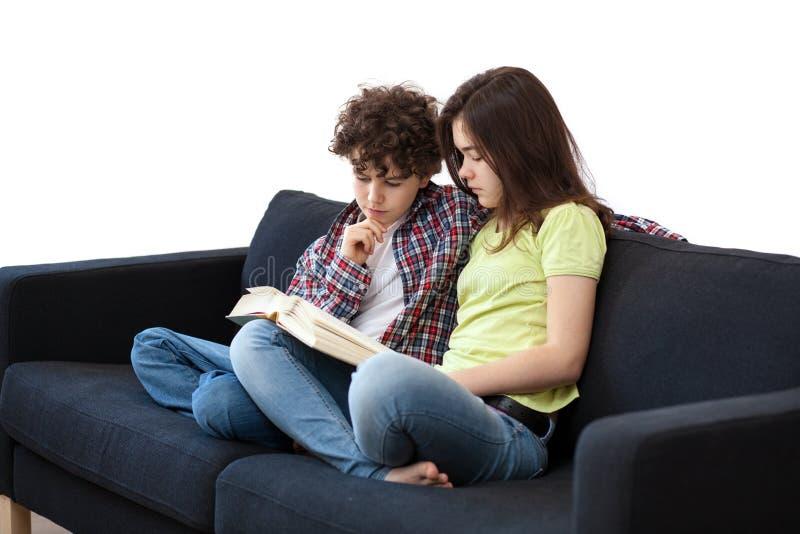 Libro de lectura de la muchacha y del muchacho imágenes de archivo libres de regalías