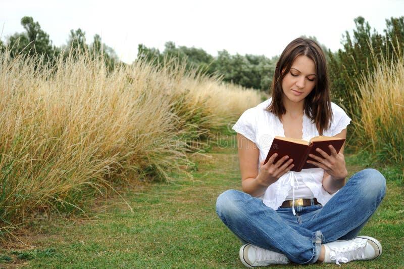 Libro de lectura de la mujer al aire libre imagenes de archivo