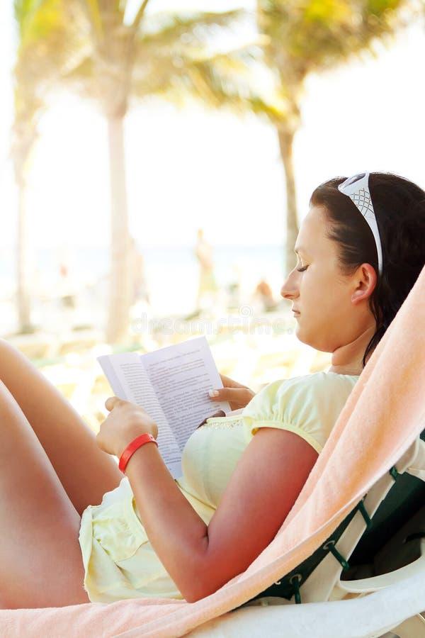 Libro de lectura de la mujer en la playa del Caribe