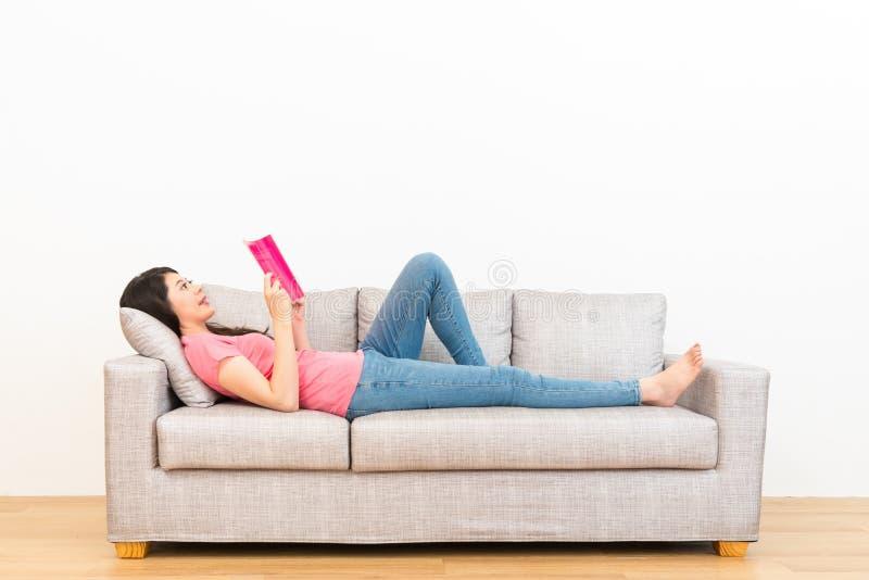 Libro de lectura de la mujer en la sala de estar que miente en el sofá foto de archivo