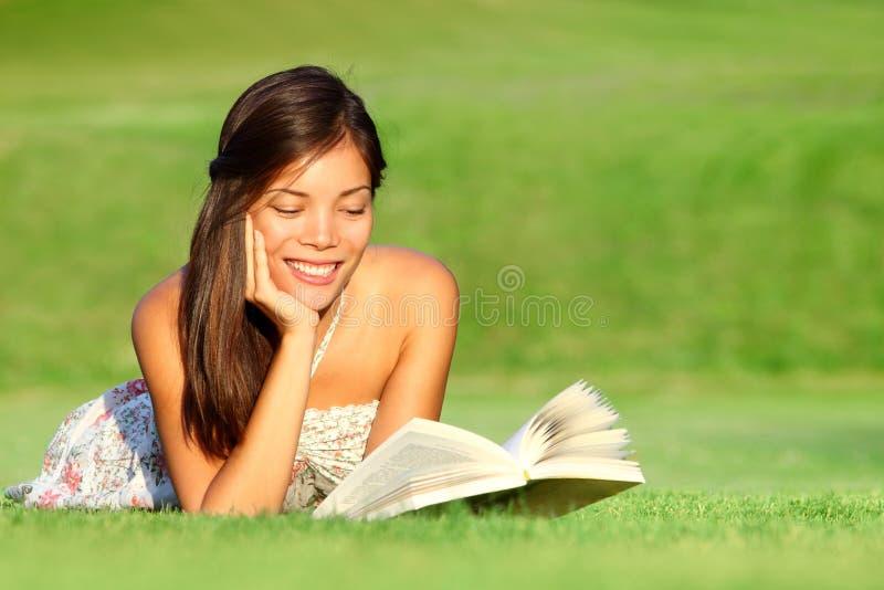 Libro de lectura de la mujer en parque imagenes de archivo